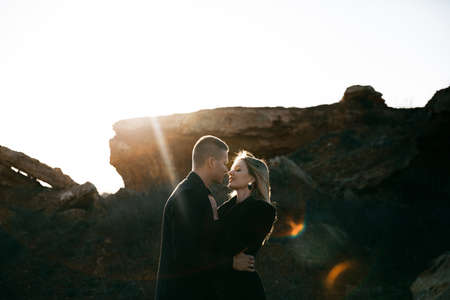 Side view portrait of two young lovers kissing by the sunset on ravine background. Couple in black clothes