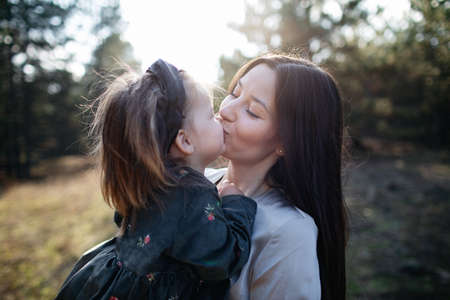 Close up portrait of beautiful dark-haired mom kisses into lips her daughter on the forest background on suslight. Parenthood. Mom hugs daughter