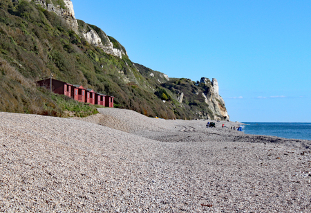 A row of beach huts on the shingle beach at Branscome in Devon, England.