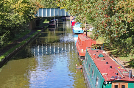 Barges moored to the bank on the Grand Union Canal at Lapworth in Warwickshire, England Stock fotó