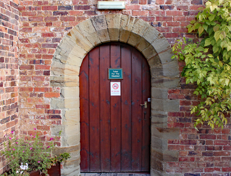 Old wooden door to disabled toilets at Arley Arboretum in the Midlands in England.