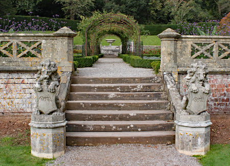 Two old stone lion statues with shields stand at the bottom of a small flight of steps.