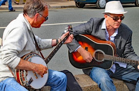 SIDMOUTH, DEVON, ENGLAND - AUGUST 8TH 2012: Two men play a guitar and a banjo on an impromptu street performance on the Esplanade 에디토리얼