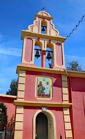 The pink bell tower of a church on the Greek island of Corfu. Standard-Bild