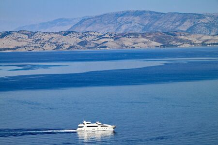 A luxury yacht passes by Corfu Town in Corfu, Greece. The mountains of Albania cane be seen in the background