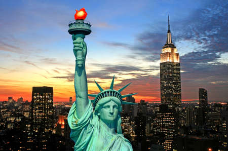 famous statues: The Statue of Liberty and New York City skyline at dark