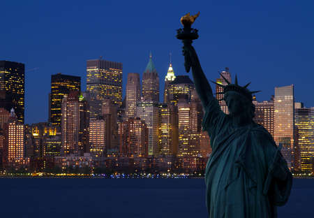 The Statue of Liberty and Manhattan Skyline at dark photo