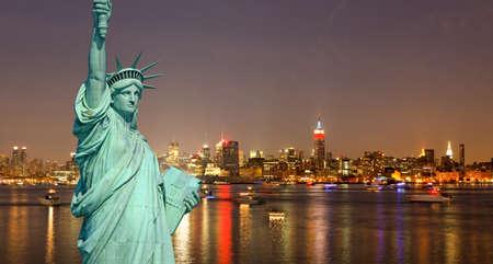 La statua della libertà e New York City Skyline di notte