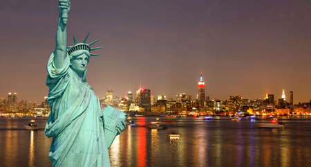 The Statue of Liberty and New York City skylines at night   Reklamní fotografie