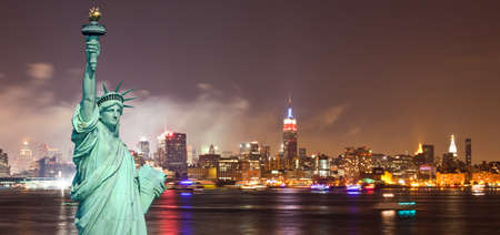 The Statue of Liberty and New York City skylines at night   Stock Photo