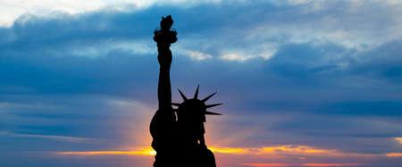 Het silhouet van de Statue of Liberty onder achtergrond zons opgang