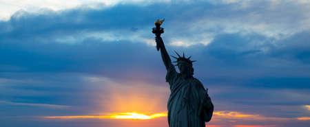 Het silhouet van de Statue of Liberty onder sunrise achtergrond