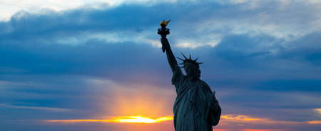 liberty: The silhouette of Statue of Liberty under sunrise background