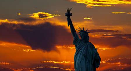 Het silhouet van de Statue of Liberty onder zons opgang achtergrond