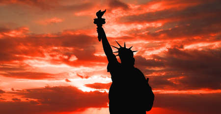 The silhouette of Statue of Liberty under sunrise background photo