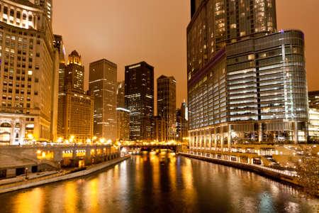 De hoge gebouwen langs de Chicago River in de nacht Stockfoto