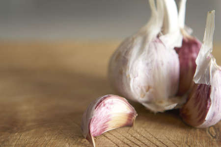 fresh garlic: Macro image of fresh garlic on rough wooden chopping board Shallow focus.