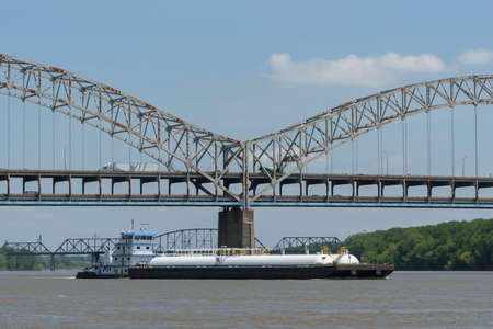 Barge passing beneather the Sherman Minton Bridge on the Ohio River in Louisville, Kentucky