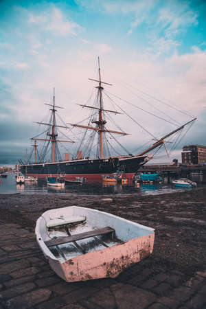 HMS Warrior moored in Portsmouth with an old fishing boat in the foreground Stock Photo