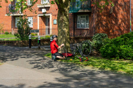 04/24/2020 Portsmouth, Hampshire, UK A cyclist repairing his bike at the roadside after getting a puncture