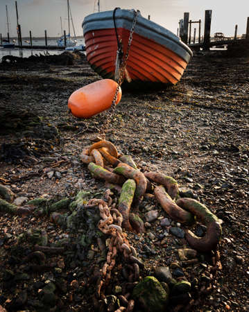 an old wooden boat chained to an anchor at low tide