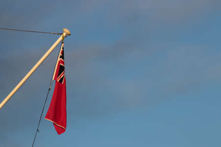 A red ensign flag flying on a fence post