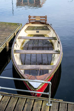 An old empty wooden rowing boat tied up on a wooden jetty on calm water