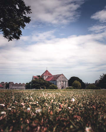 An old English church surrounded by fields with blue sky and white clouds