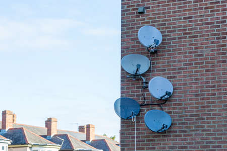 A Group of satellite dishes on the side of a brick building