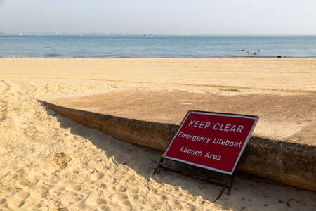 a sign at the side of a slipway on a beach with a sign saying keep clear emergency lifeboat launch area