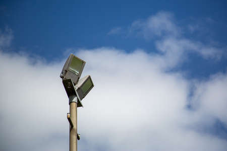 Floodlights above a football pitch with blue sky and clouds in the background