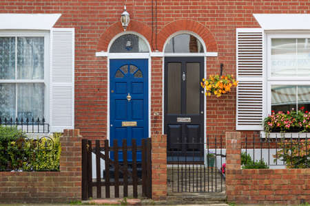 The doorway or entrance to typical Victorian terraced housing showing the front gate and windows with shutters Imagens
