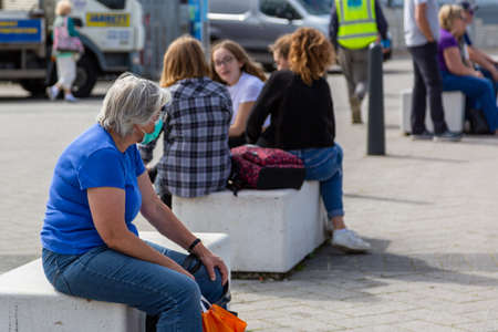 09/08/2020 Portsmouth, Hampshire, UK A middle aged woman resting while shopping wearing a medical face mask with a group of teens in the background not wearing face coverings