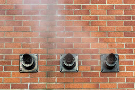 Three central heating boiler flues releasing steam on the exterior of a brick house