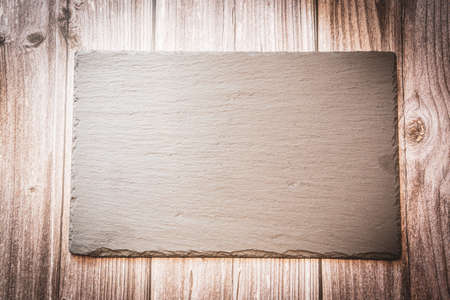 A slate plate on a wooden background with copy space Stock Photo