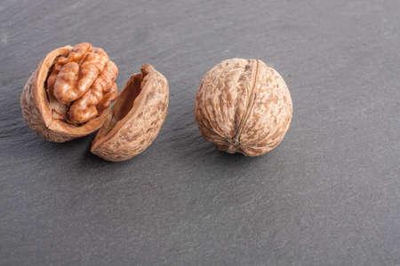 Walnuts, chopped nut on a slate plate on a dark background close-up Reklamní fotografie