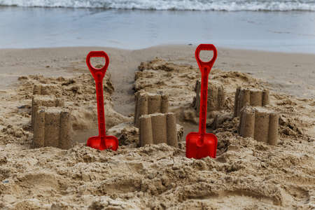 children sandcastle: buckets and spade with sandcastles on the beach at courtown, wexford, ireland Stock Photo