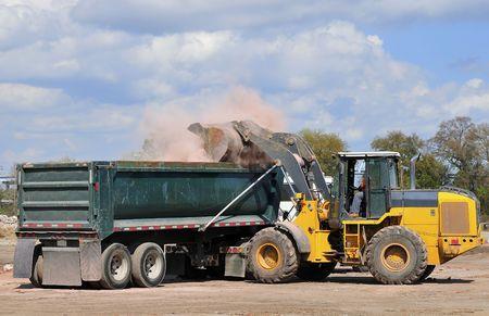 front end loader: A large front end loader loading waste bricks into a dump truck