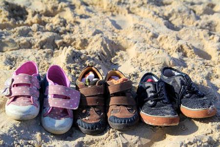Tres pares de zapatos y calcetines para niños perfectamente a la izquierda en una playa soleada