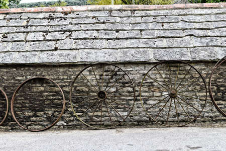 thresh: Row of old farm wheels leaning against a rustic old stone building