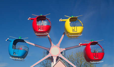 Funfair helicopter ride against a bright blue sky