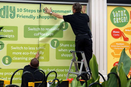 put up: CAMBERLEY,ENGLAND, June 07 2016: Two men put up environmental posters in a shopping mall