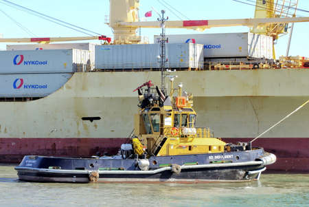 alongside: PORTSMOUTH, ENGLAND, MAY 29 2016: Tugboat SD Indulgent alongside a container ship