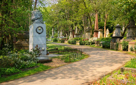 consecrated: HIGHGATE, LONDON, UK - March 12, 2016: Path leading through the East Cemetery past the memorial to Karl Marx