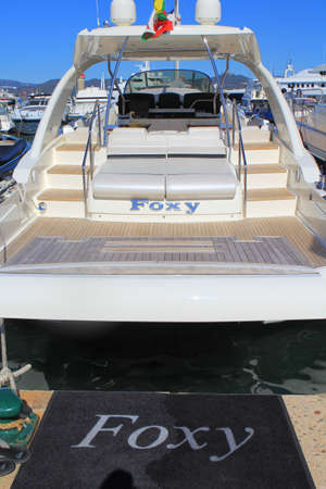 tropez: SAINT-TROPEZ, PROVENCE, FRANCE - AUGUST 21, 2016: Rear view of a small luxury power boat moored in the new port of St Tropez