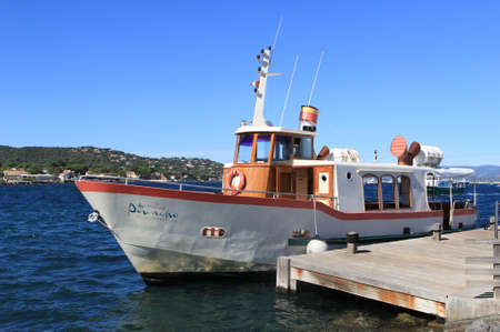 SAINT-TROPEZ, PROVENCE, FRANCE - AUGUST 21, 2016: An older style motor boat moored at the jetty in St Tropez