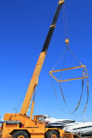 tropez: SAINT-TROPEZ, PROVENCE, FRANCE - AUGUST 21, 2016: A boat crane rising high against the blue sky, ready to winch a powerboat from the port at St Tropez
