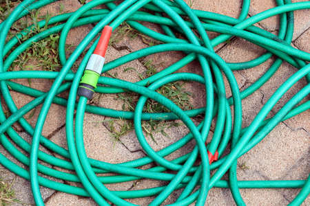 Green garden water hose with red and white nozzle coiled up untidily on a stone block background with weeds. Stock Photo