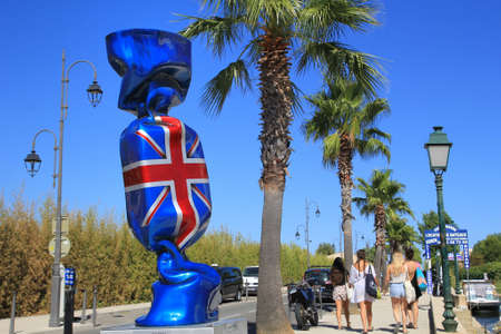 laurence: PORT GRIMAUD, PROVENCE, FRANCE - AUGUST 23 2016: Giant sweet candy sculpture with Union Flag wrapper, by French artist Laurence Jenkell in this pretty French Riviera village built on the shore of the Mediterranean