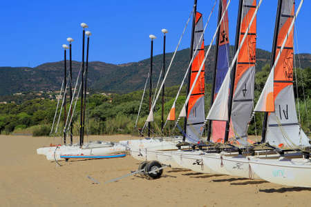 dinghies: LA CROIX VALMER, PROVENCE, FRANCE - AUGUST 23 2016: Sailing dinghies from a yachting school in early morning sun on the beach at La Croix Valmer, on the French Riviera Editorial